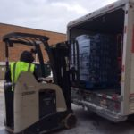 Volunteer driving a high lo forklift unloading a pallet of bottled water from truck