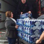 MDT employees unloading bottled water from storage truck