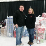 Photo of two MDT employees standing in front of bagged donated gifts