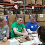 Employees folding shopping bags for Canned Food Drive at Gleaners - 2019
