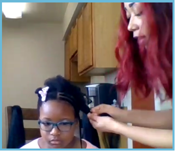 MDT employee braiding a young girl's hair