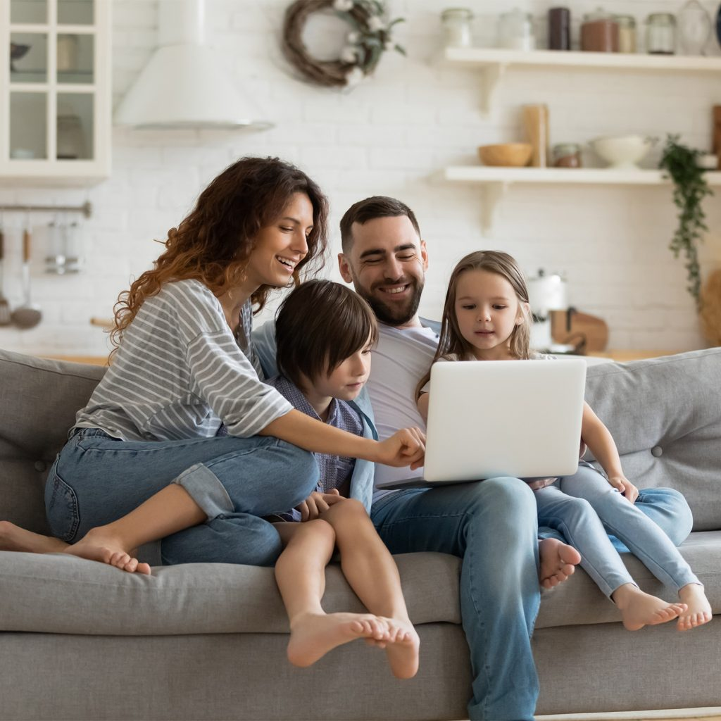 Family with kids sit on sofa with laptop